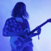 A man plays guitar in a purple light.