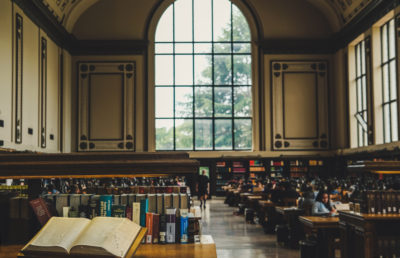 The inside of a library shows rows of people reading and studying.