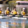 A group of athletes row a boat through a body of water.