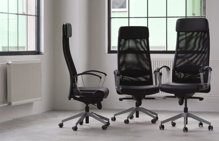 Three empty office chairs sit in a white room.