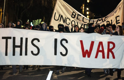 "Protesters holding a ""This is War"" sign at the 2017 Berkeley Milo"