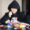 Photo of an individual eating candy in a hoodie
