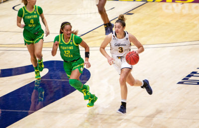 Photo of Dalayah Daniels of Cal Women's Basketball dribbling against an Oregon defender