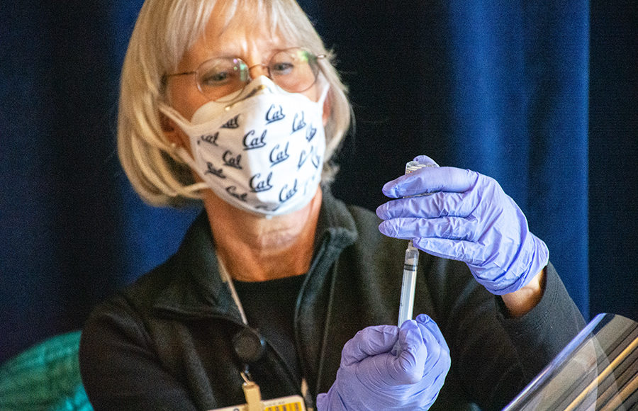 Photo of a women holding a syringe with the COVID-19 vaccine