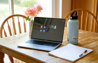 Photo of computer with zoom open alongside a notebook and a water bottle