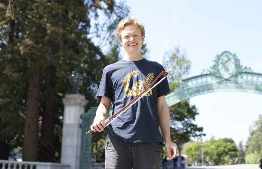Photo of Paul Nicknish holding a bow in front of Sather Gate