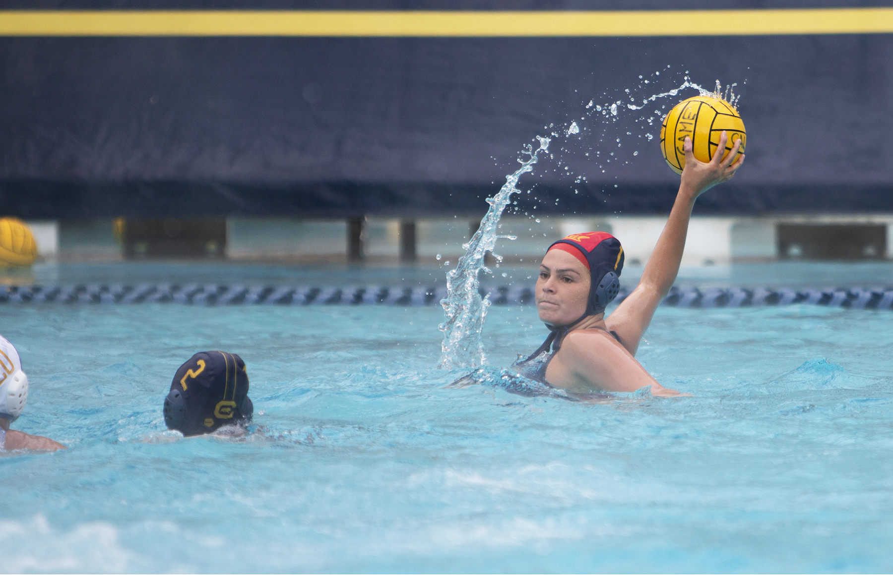 Photo of Cal Women's Water Polo player preparing to throw the ball