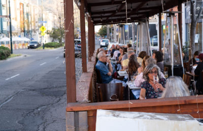 photo of people eating outside of a restaurant