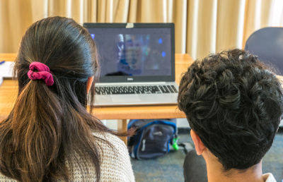 photo of 2 people watching a movie on a laptop