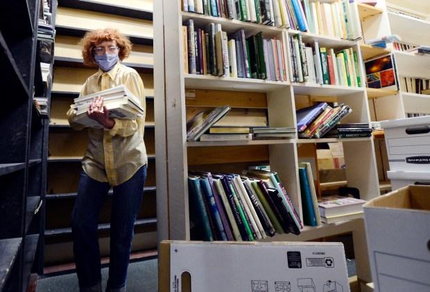 Volunteer, Toni Oswald, packs up books ...