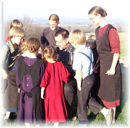 Amish children viewing photos.