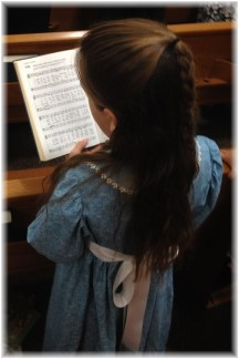 Child singing from hymnal