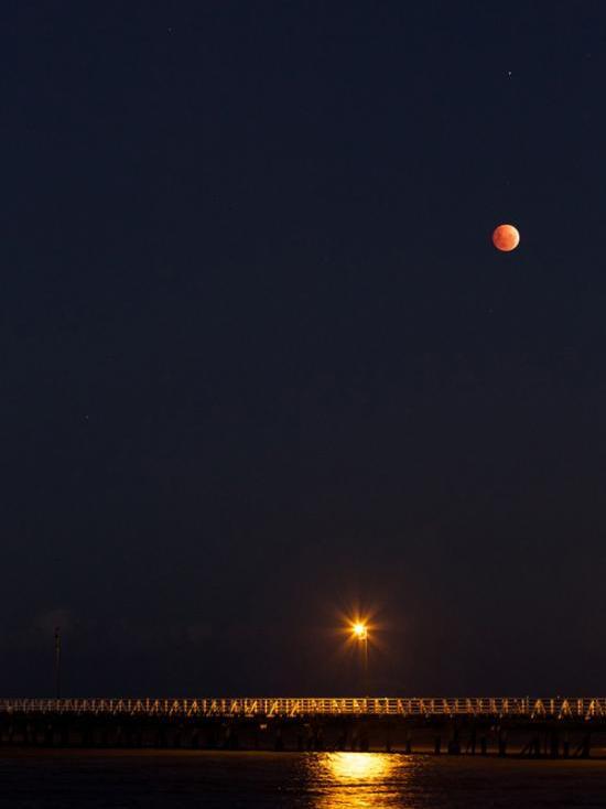 Blood Moon rises over the ocean off Brisbane, Australia
