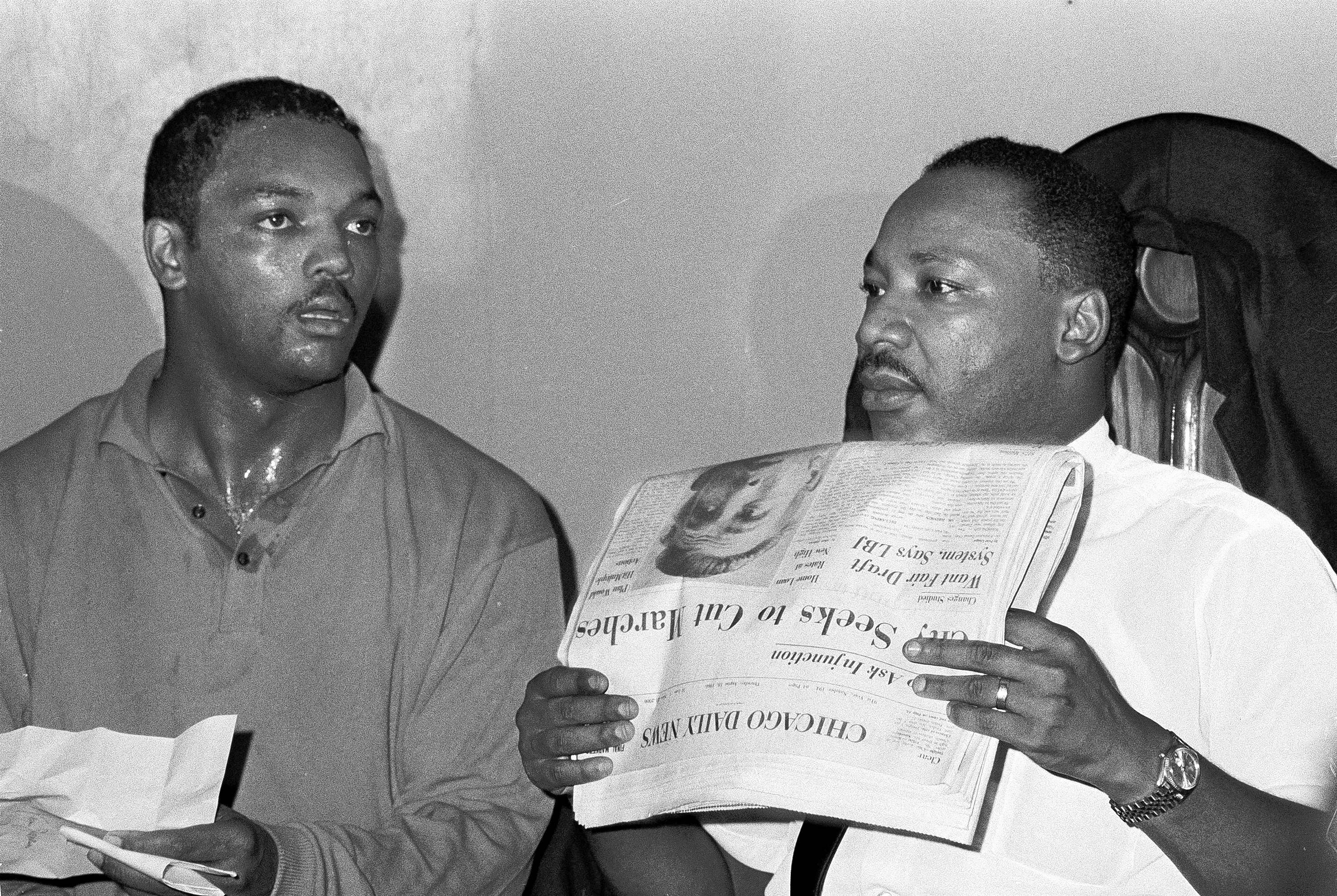 "The Rev. Martin Luther King Jr. and the Rev. Jesse Jackson in Chicago. King holds a Chicago Daily News paper with a headline that reads ""City Seeks To Cut Marches."