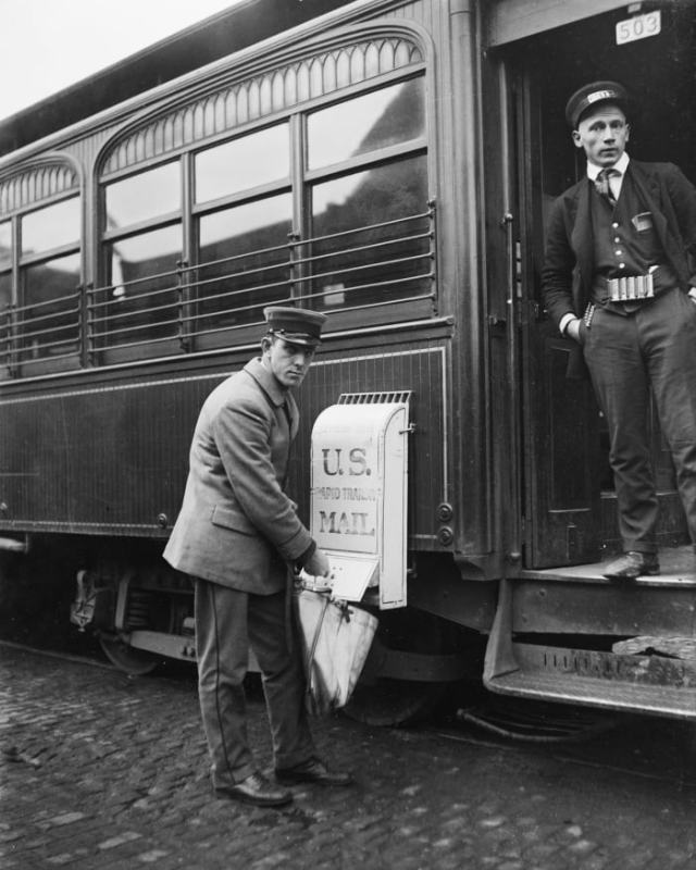 A postman collects letters from a train mailbox, circa 1921.