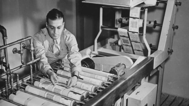 A man uses a continuous paper-processing machine to develop, repair, wash and dry paper reproductions of microfilmed emails at the Pentagon in Washington, DC, February 1943.