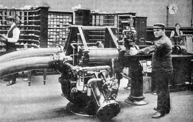 An operator prepares to feed a carrier containing about 500 letters into the transmitter for shipment through the tube from the Brooklyn Post Office to the New York General Post Office, a distance of about 1.75 miles, circa 1899.
