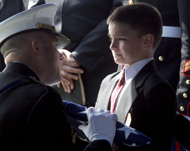 When 8 year-old Christian Golczynski accepts the flag for his father, Marine Staff Sgt. Marc Golczynski, who died in Iraq