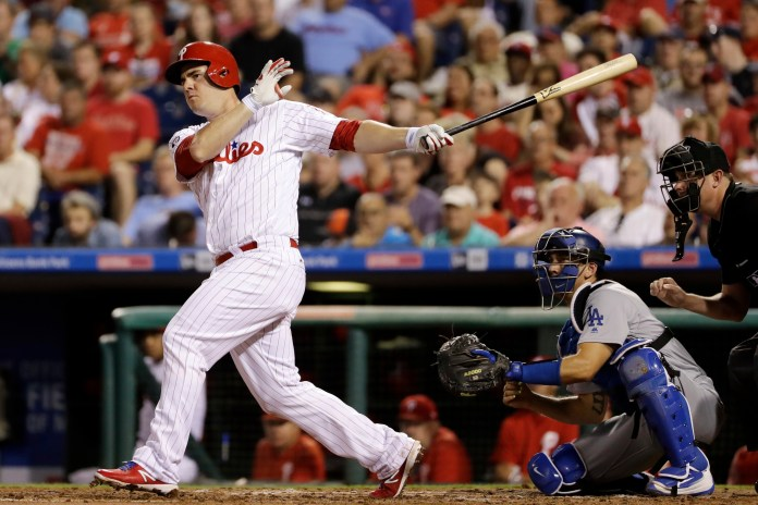 Philadelphia Phillies' Tommy Joseph, left, follows through on an RBI double off Los Angeles Dodgers starting pitcher Alex Wood during the second inning of a baseball game, Wednesday, Sept. 20, 2017, in Philadelphia. At right is catcher Austin Barnes. (AP Photo/Matt Slocum)
