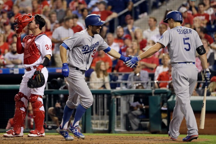 Los Angeles Dodgers' Chris Taylor, center, celebrates with Corey Seager, right, past Philadelphia Phillies catcher Andrew Knapp after Taylor's home run off starting pitcher Jake Thompson during the third inning of a baseball game, Wednesday, Sept. 20, 2017, in Philadelphia. (AP Photo/Matt Slocum)