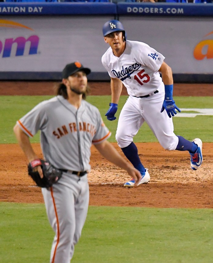 Los Angeles Dodgers' Austin Barnes, right, runs to first after hitting a solo home run while San Francisco Giants starting pitcher Madison Bumgarner watches during the eighth inning of a baseball game, Saturday, Sept. 23, 2017, in Los Angeles. (AP Photo/Mark J. Terrill)