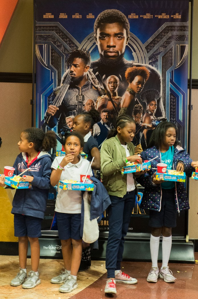 A group of kids holds their popcorn and sodas before entering an IMAX theater as the Boys & Girls Club watch the Black Panther movie at a special Boys & Girls Club IMAX screening in Long Beach Thursday, February 15, 2018. As part of the viral #BlackPantherChallenge campaign, IMAX, Regal Entertainment Group, Walt Disney Pictures and Marvel Studios, hosted an advance IMAX screening of Black Panther for the Boys & Girls Club Long Beach. Club members got to see the film before its nationwide release. (Photo by Thomas R. Cordova / Daily Breeze)