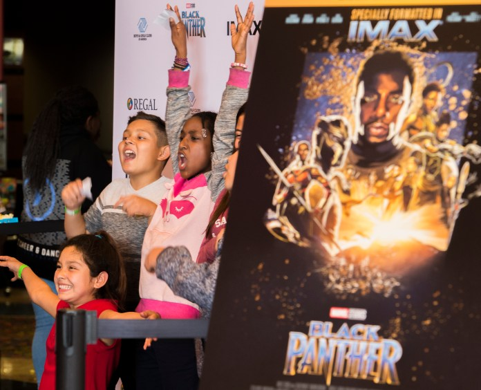 Kennedi Bryant, right, holds her arms up along with Owin Ayala, left and Isabel Dehoyas, front, as the Boys & Girls Club members get excited to watch the Black Panther movie at a special Boys & Girls Club IMAX screening in Long Beach Thursday, February 15, 2018. As part of the viral #BlackPantherChallenge campaign, IMAX, Regal Entertainment Group, Walt Disney Pictures and Marvel Studios, hosted an advance IMAX screening of Black Panther for the Boys & Girls Club Long Beach. Club members got to see the film before its nationwide release. (Photo by Thomas R. Cordova / Daily Breeze)