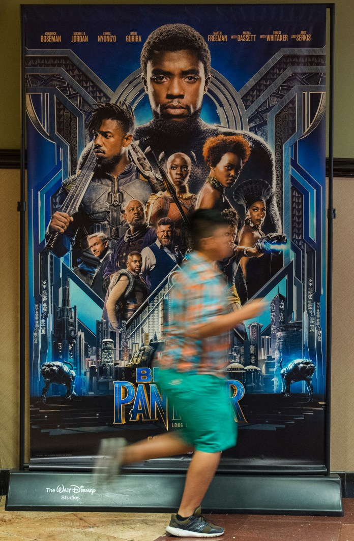A boy runs past a movie poster as the Boys & Girls Club watch the Black Panther movie at a special Boys & Girls Club IMAX screening in Long Beach Thursday, February 15, 2018. As part of the viral #BlackPantherChallenge campaign, IMAX, Regal Entertainment Group, Walt Disney Pictures and Marvel Studios, hosted an advance IMAX screening of Black Panther for the Boys & Girls Club Long Beach. Club members got to see the film before its nationwide release. (Photo by Thomas R. Cordova / Daily Breeze) nationwide release. (Photo by Thomas R. Cordova / Daily Breeze)