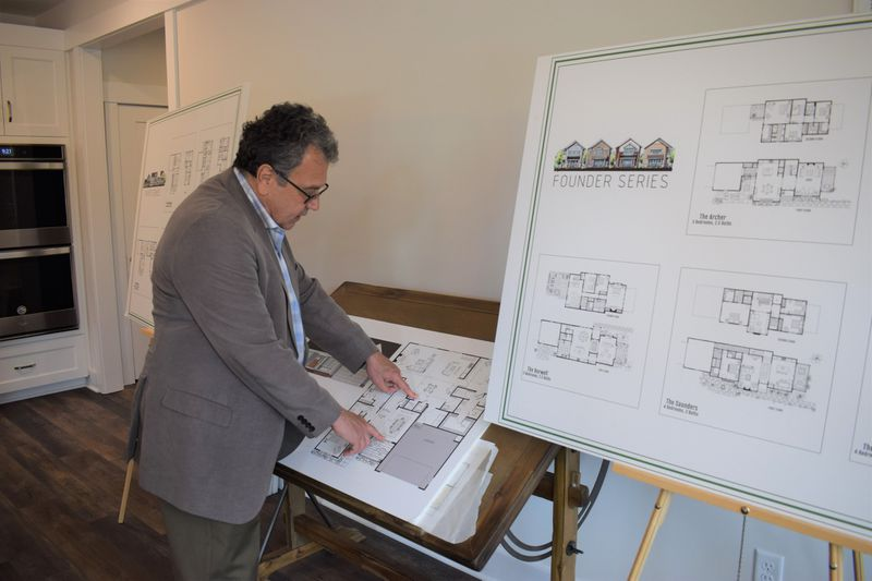 Healthy Communities President Jay Epstein looks over one of the home designs available at Walnut Farm. Ben Swenson/freelance