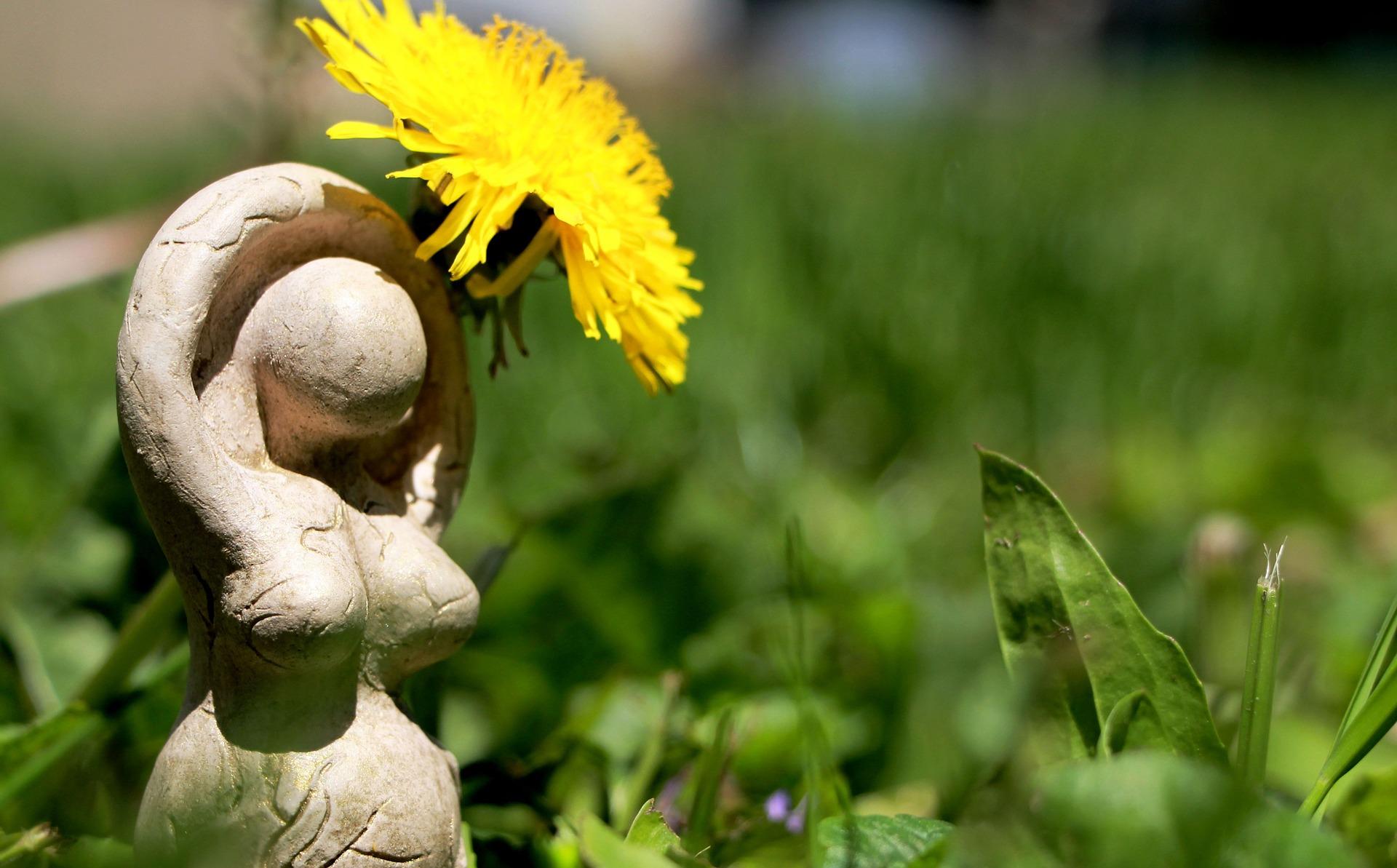 Mutter Natur Statue steht neben Löwenzahnblüte