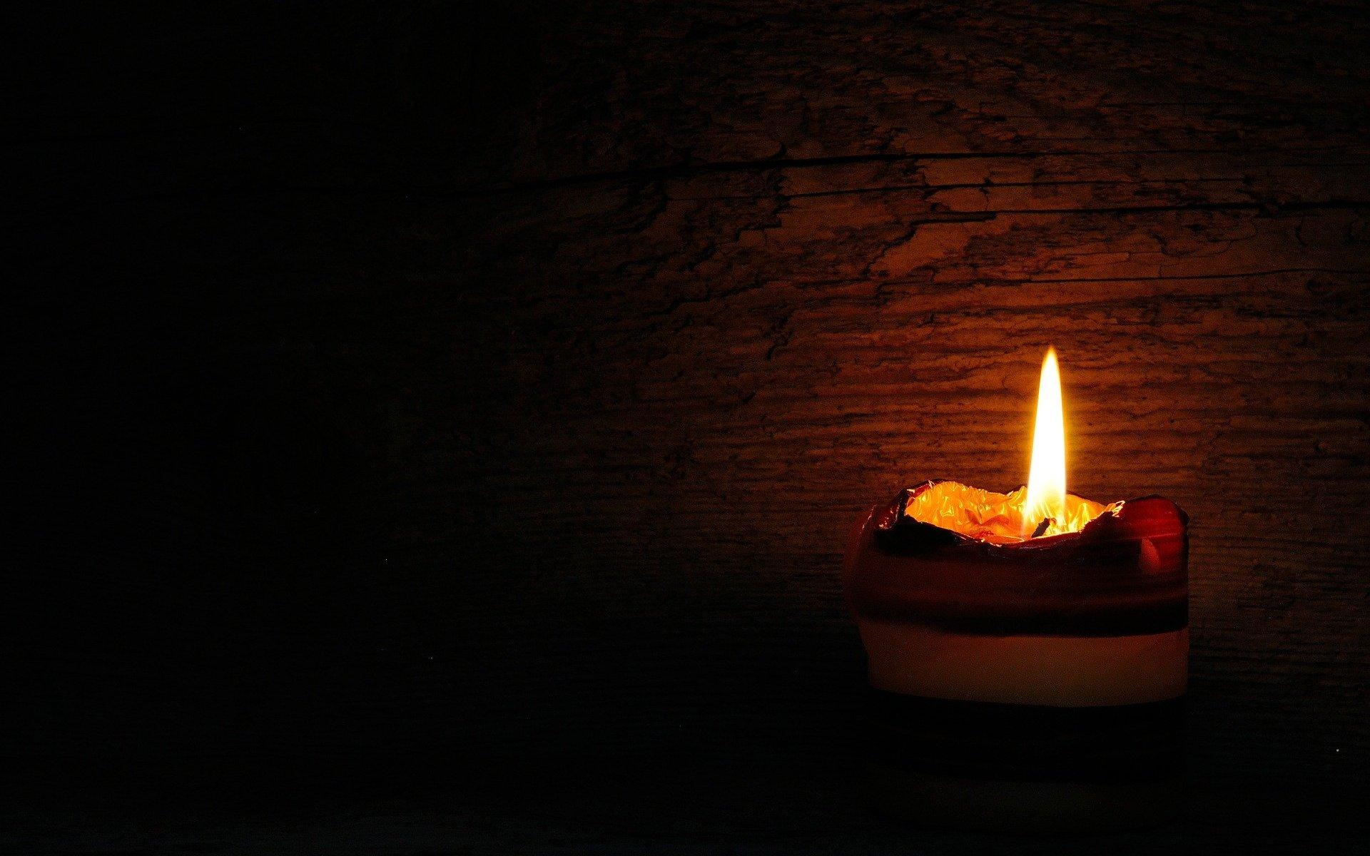 Das Imbolc-Symbol - eine brennende Kerze - erleuchtet in der Dunkelheit eine Holzwand.