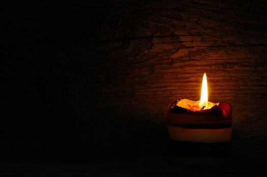 Brennende Kerze vor einer dunklen Holzwand. Ob sie für Imbolc angezündet wurde?