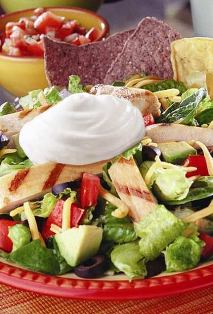 grilled chicken nacho salad on plate with chips