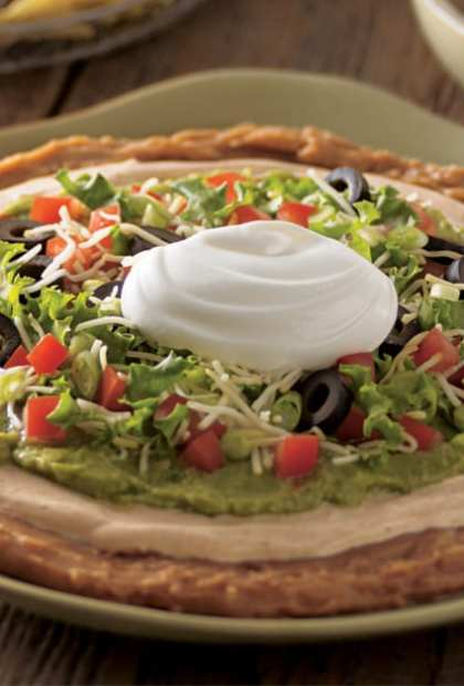 Mexican Layered bean dip on plate with sour cream on top