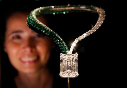 """A staff member poses behind """"The Art of de Grisogono,"""" a necklace suspending a 163.41-carat, D color, flawless, IIA type diamond, during a preview of Christie's auction sale in Geneva"""