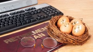 Retirement-IRA-401k-pension-plan-book-and-nest-egg-with-computer (1)