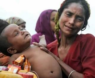 Seorang wanita muslim Rohingya Myanmar berada dalam sebuah perahu bersama bayinya dalam pelariannya ke Bangladesh