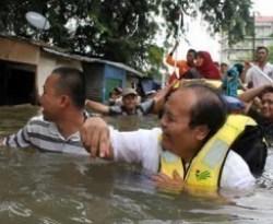 Ketua Fraksi Partai Keadilan Sejahtera (PKS), Hidayat Nur Wahid menerobos banjir untuk memberikan bantuan kepada warga korban banjir di Posko PKS Petamburan, Jakarta, (18/01). (ANTARA)