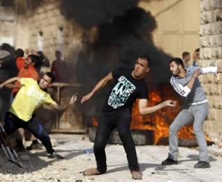 Warga Palestina melempar baru dekat ban yang terbakar ketika bentrok dengan pasukan Israel di dekat Jenin. (yahoo.com)
