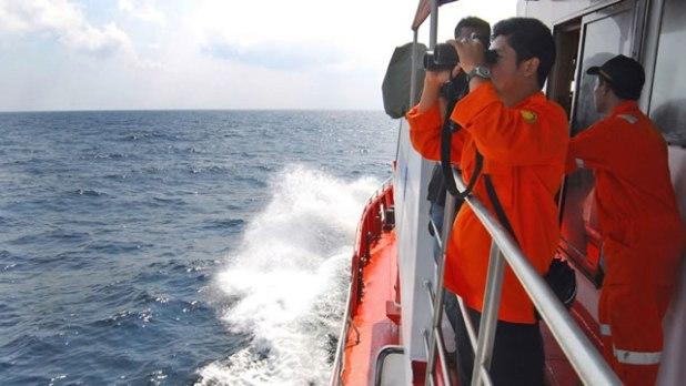 Seorang anggota Badan SAR Nasional (Basarnas) menggunakan teropong untuk melihat cakrawala selama operasi pencarian untuk pesawat Malaysia Airlines Boeing 777 yang hilang. Operasi dilakukan di perairan Selat Malaka dari Pulau Sumatera, Indonesia, Rabu (12/3/2014). (Foto: Heri Juanda/Associated Press)