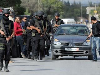 Anggota polisi yang berjaga-jaga di bawah rumah tempat pelaku terorisme bertahan (aljazeera.net)