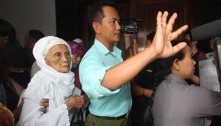 Nenek Fatimah dijaga oleh keluarganya saat berjalan keluar usai menjalani persidangan di Pengadilan Negeri Kota Tangerang, Banten, 30 September 2014.  (TEMPO/Marifka Wahyu Hidayat)