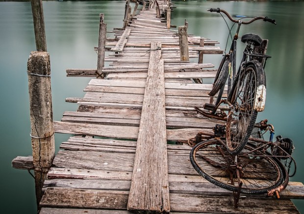 Foto eines mehrfach geflickten, nicht Vertrauen erweckenden Holzsteiges, der über ein grünes Wasser führt.