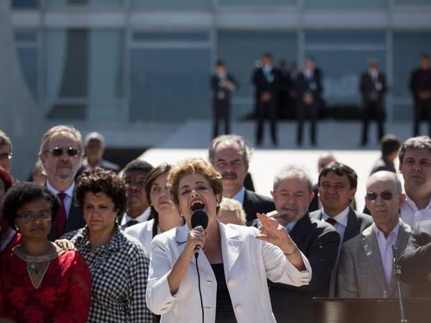 Dilma ao lado de Lula e de outros apoiadores durante sua saída do Palácio do Planalto, em Brasília (Foto: Felipe Dana/AP)