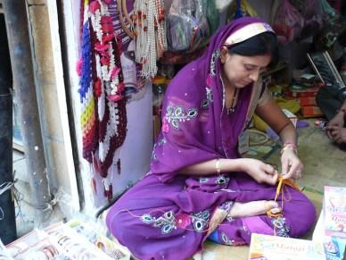 'artigiana crea un braccialetto utilizzando le dite dei piedi