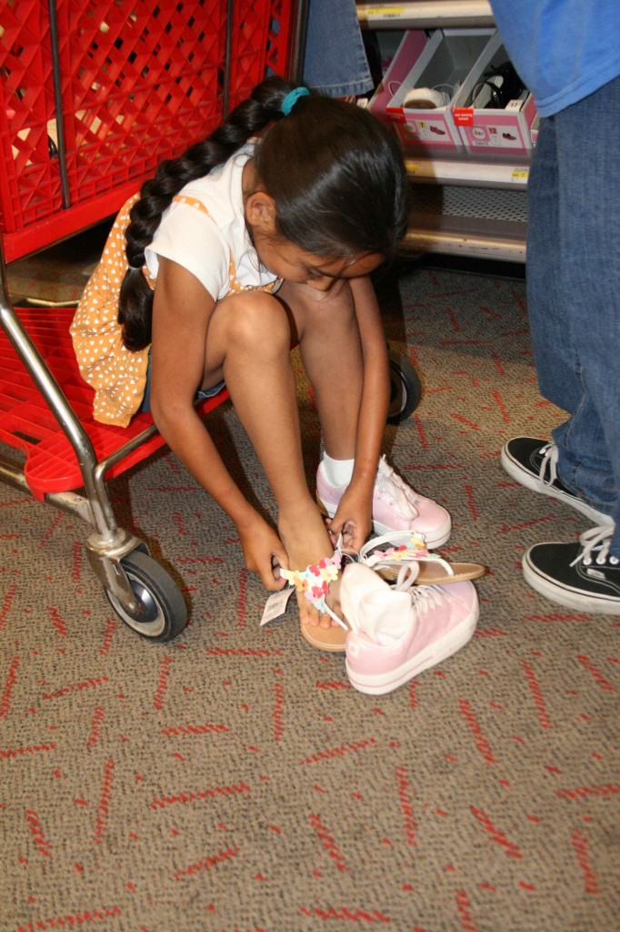 A little girl tries on a pair of sandals at the 499 W . Orange Show San Bernardino Target <a style=