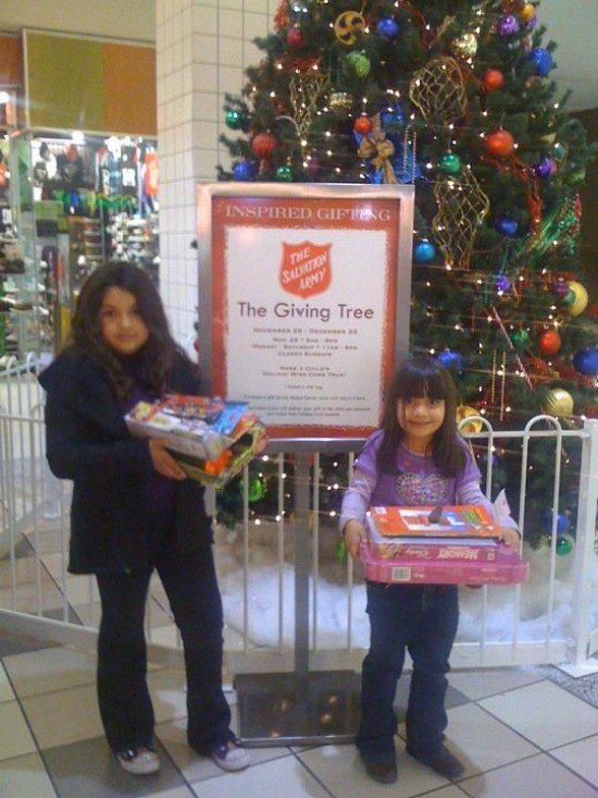 Arlene and Priscilla Delgado, ages 4 and 8, each used their savings to purchase Christmas toys for a less fortunate child through the Salvation Army San Bernardino Corp's Giving Tree program at Inland Center Mall. Help the Salvation Army obtain more toys for children in need by going to the Giving Tree near the mall's Food Court. Photo by Kelly Silvestri-Raabe