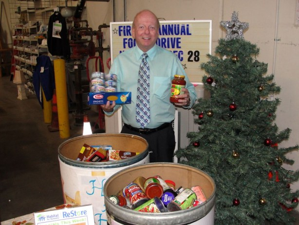 Habitat for Humanity Executive Director Dennis Baxter shows off some the non-perishable food donated for discounts from The Habitat for Humanity ReStore.  Food is donated to the Second Harvest for its holiday Food Drive,