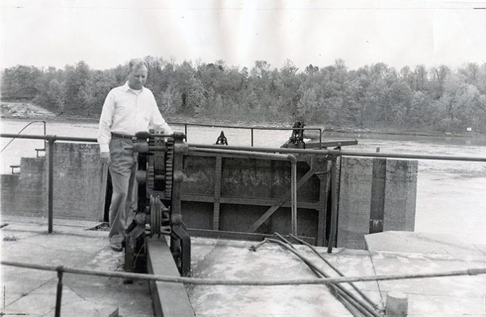 "Photograph from May 1, 1960, Kansas City Star.  The caption reads: ""The new owner of Osage Lock and Dam No. 1 looks over a part of his property. James N. Rice of Jefferson City ""private eye"" and avowed fisherman, examines part of the rusty mechanism that opens and closes the locks on the Osage River near the capital city."