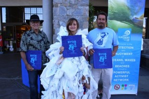 City Councilman Steven Weinberg, Dana Hills Surfrider Foundation Club member Grace Willett and Rick Erkeneff, Surfrider Foundation South Orange County Chapter chairman, hand out free reusable shopping bags the first day of the single use plastic bag ban. Photo by Elysia Gamo